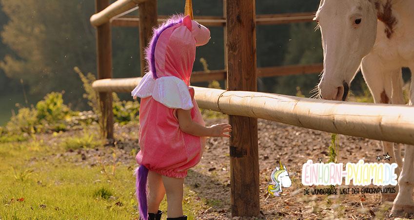 Kind im Einhorn Pyjama mit Pferd auf einer Wiese
