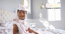 Kleines Kind trägt einen Einhorn Pyjama im Bett