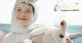 Onesie Einhorn Pyjama - Kind mit kleinem Einhorn beim spielen