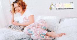 Frau im Bett mit Schlafanzug mit Einhorn Motiv an
