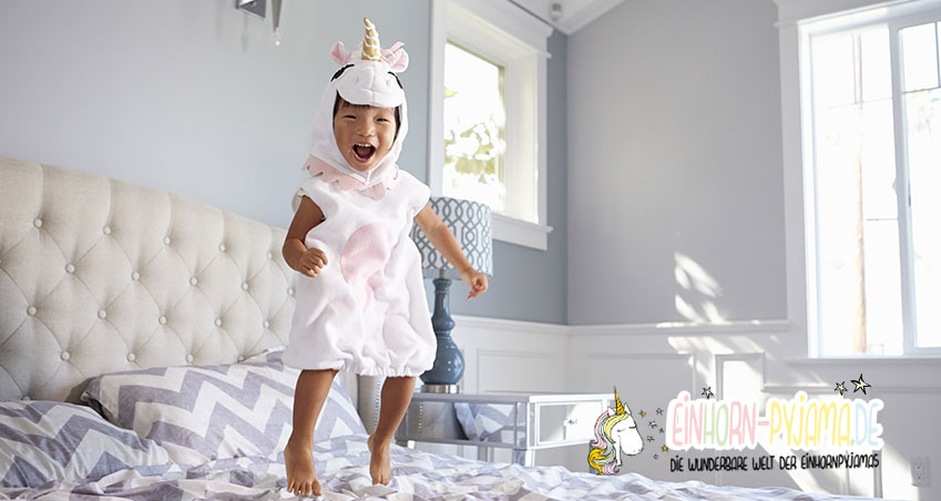 Kleines Kind mit Einhorn Schlafanzug hüpft auf Bett