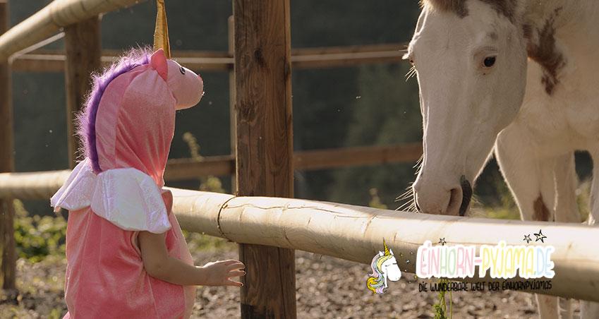 Kind mit rosa Einhorn Pyjama auf einer Pferdeweide